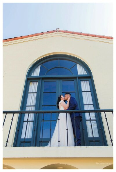 Catalina country club wedding, in the spring. This photo was photographed by Marianne Lucas photography in Los Angeles.  Bride & groom photo standing on the balcony of the country club. With the venue name showing in the picture.
