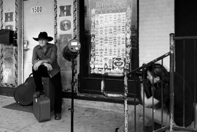 Country music photography behind the scenes Mark Maryanovich sitting on stairs while photographing Darrell Goldman sitting on suitcase guitar leaning beside him black and white image