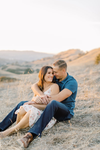 Bride and groom snuggle on a golden hillside during their engagement session in Walnut Creek California