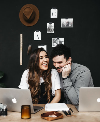 A+C-brandshoot-9-WEB-seattle-wedding-photographers-black-wall-hat-desk-layout-laugh-candid-couple-goals-cute-work-together-business