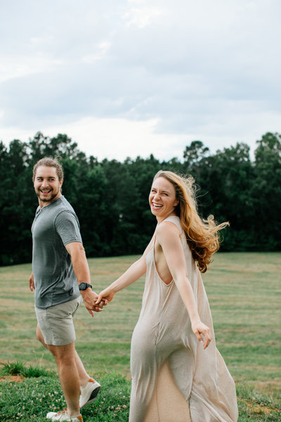 man and woman smiling while walking through field holding hands
