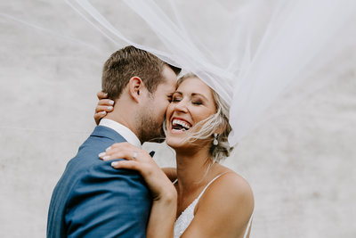bride laughing as groom whispers in her ear under veil