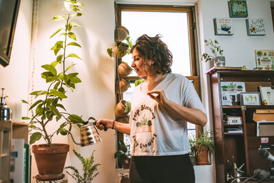 woman waters her plants in her apartment