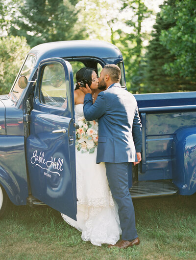 Bride & groom share a kiss at their Gable Hill wedding in front of blue truck photo by wedding photographer in Grand Rapids Cynthia Boyle