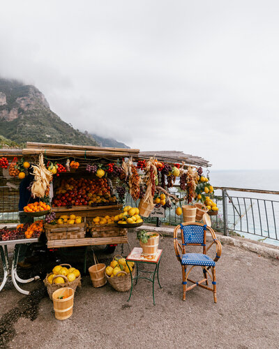 fruit stand with lemons and oranges and blue chair