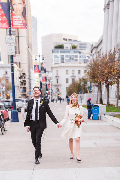 happy couple walking down street after sf city hall wedding ceremony