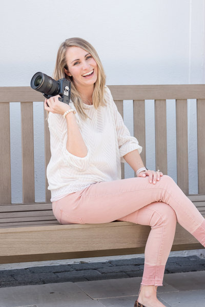 Photographer Amanda Zabrocki smiles with her camera sitting on a bench outdoors
