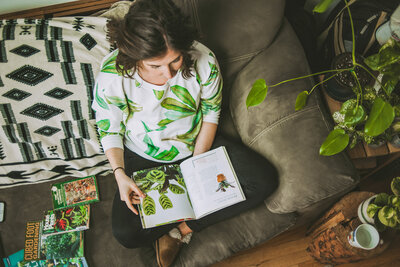 woman reads plant book on her sofa