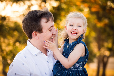 Outdoor portrait of dad holding smiling daughter