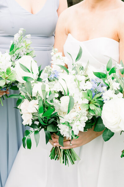 bride holding white and blue bouquet