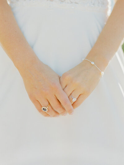 bride holding hands and showing wedding ring off