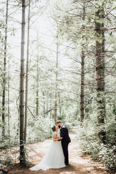 kortright center bride and groom kissing in forest