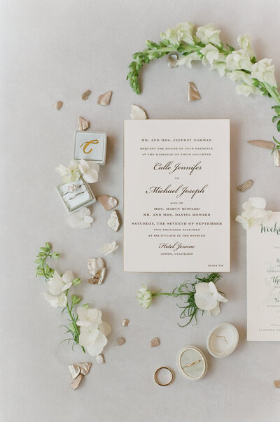 Flat-lay of white wedding invitation with cursive writing, green stems, white flowers and pink flower-petals, and wedding rings