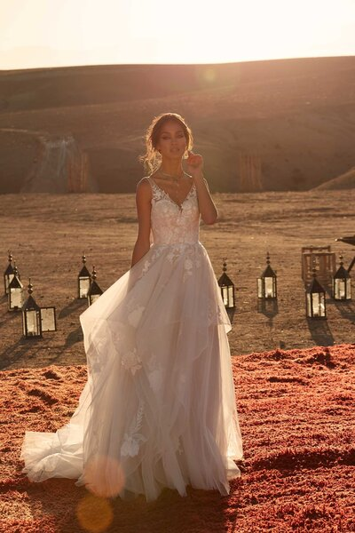 For the princess bride in all of us, set your dreams alive with Aubrey. Her magical tiered layered skirt billows blissfully in the warm desert breeze. She is innocent and saintly standing tall against the red desert. Her shimmering rose appliques climb romantically across her bodice and up the sheer straps before dipping down the back into the same V as seen on the neckline. On a closer look, through the body of the tiered skirt rose motifs hide among the many layers of Aubery – making her a vision as she turns and dances the night away.