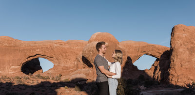man and woman standing in front of natural rock arch
