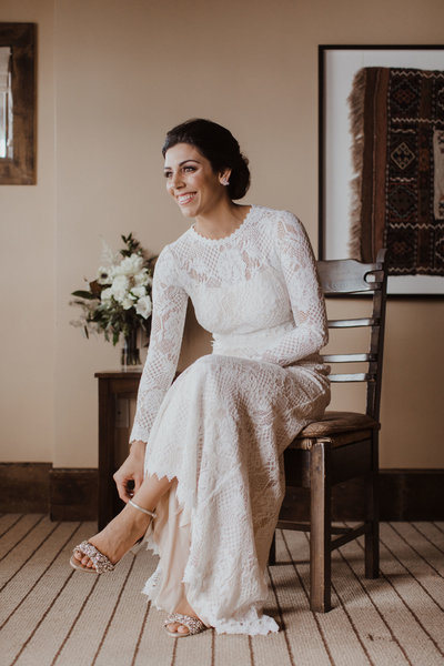 bride sitting on chair smiling and touching her shoe