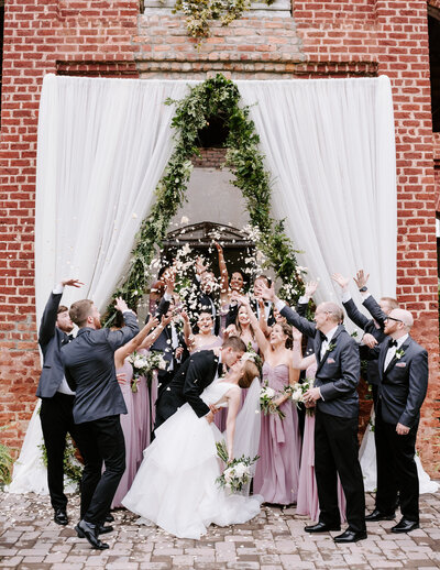 bride and groom kissing while surrounded by bridal party
