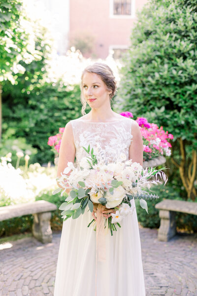 Bride with her lush wedding bouquet in Amsterdam's whimsical garden for a styled city elopement shoot organized by Lovely & Planned