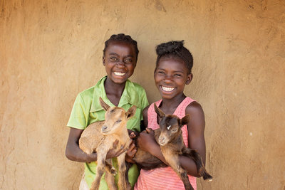 Two children holding goats during humanitarian photoshoot