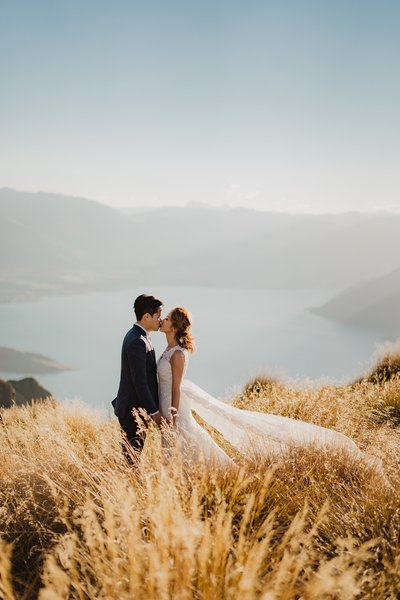 Bride and groom in the long grass above lake wakatipu