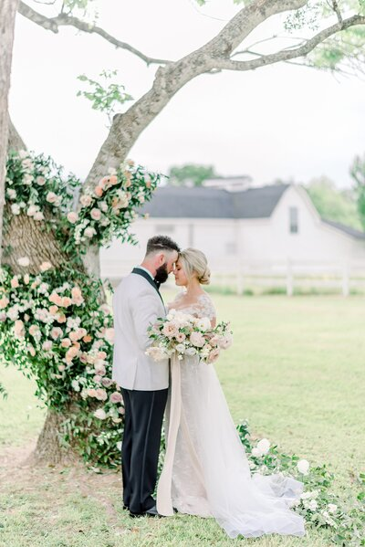 bride and groom on their wedding day under lush greenery cascading down a tree at white barn venue bydallas  photographer wedding Catie Ann Photography