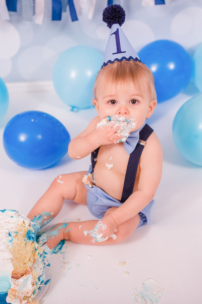 Little boy smashes cake into his mouth during cake smash photography session