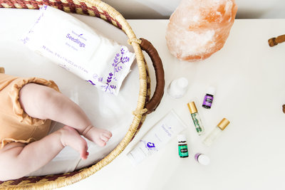 Collection of essential oils and a baby in a basket