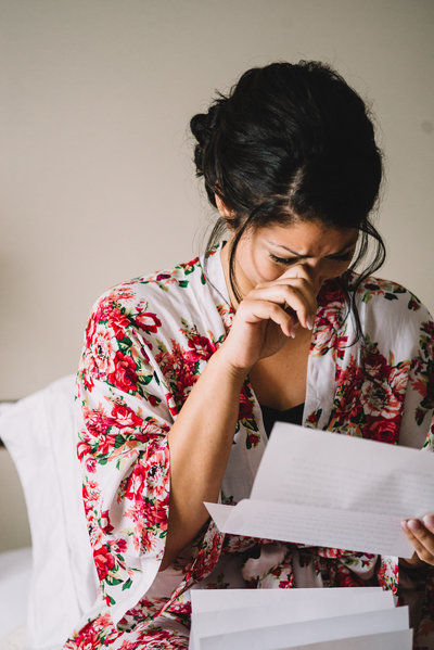 woman holding letter while crying