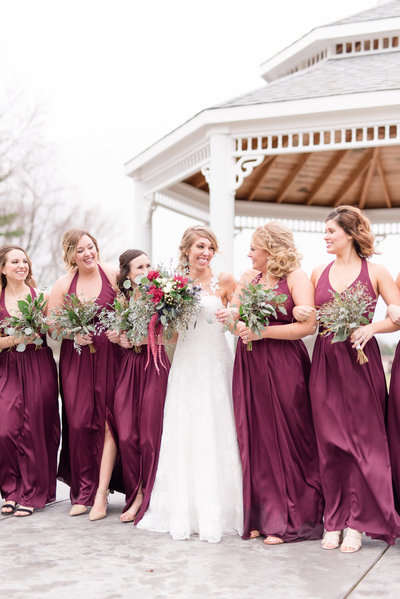 Bride and bridesmaids walk together.