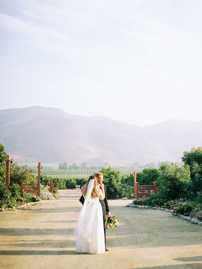 Bride and groom standing in ranch gardens with mountains in the background.