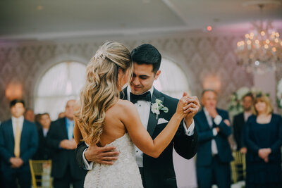 bride in white dress shares first dance with groom in black tux in a large ballroom at the merion shot by wedding photographer in philadelphia alex medvick