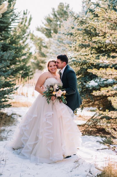 bride and groom kissing snow