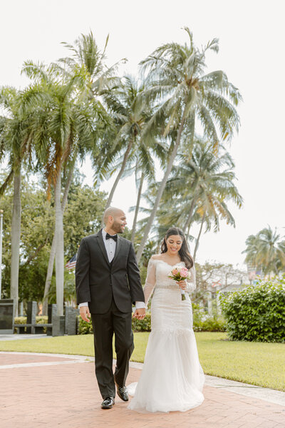 Bride and groom smile at each other and hold hands underneath palm trees