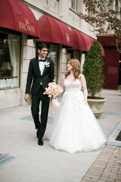 bride and indian groom walk down the street outside the brown hotel in louisville