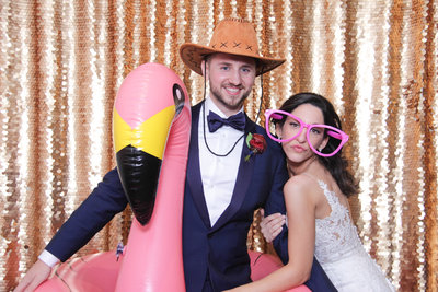 couple posing front of a gold backdrop with a flamingo float as a prop