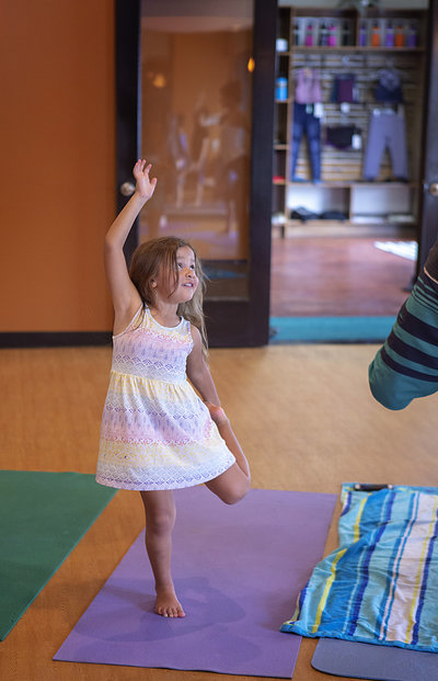 Little girl smiles and holds yoga stretch