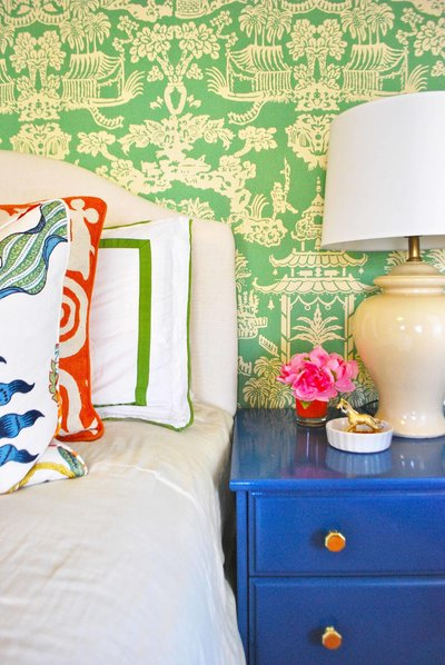 A bed and blue night stand in front of green wallpapered wall.