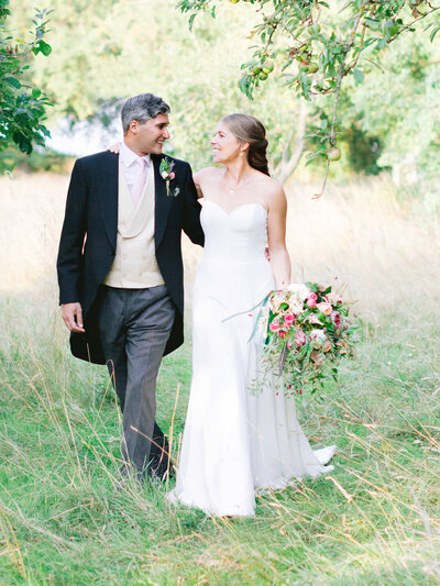 Soft and romantic wedding portrait in a beautiful apple orchard during golden hour