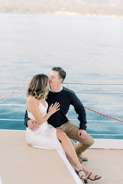 couple sitting and cuddling on boat during their engagement session