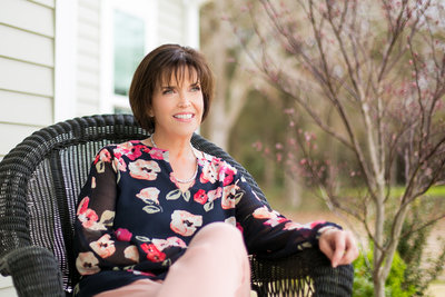 Realtor in a floral blouses poses for photo in a wicker chair