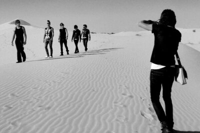 Behind the Scenes Band photoshoot Mark Maryanovich photographing My Darkest Days members as they walk in single file across sand dune black and white image