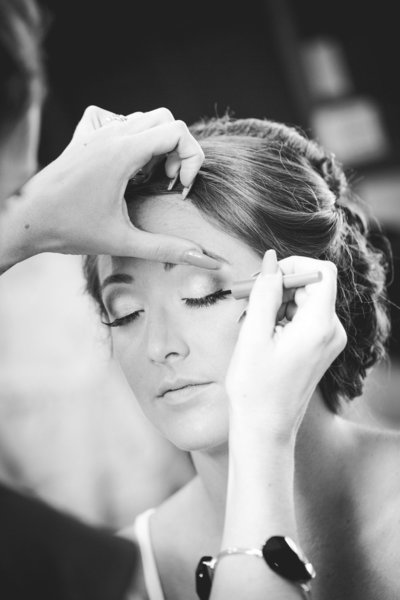 Black and white portrait of bride getting her makeup done