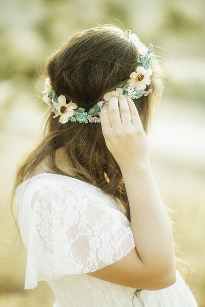 woman in white maternity dress holding flower crown of her head in Malibu California