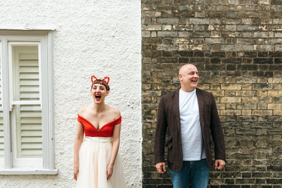 Lisa and Neil stand in front of a brick wall in Norwich and laugh. Lisa wears red cat ears and Neil wears a blazer.