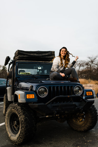 woman sitting on jeep smiling