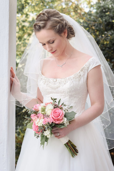 bride and pink bouquet on the front porch of the Golden Horseshoe Inn wedding venue