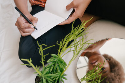 Black woman sitting by a plant writing in a notebook