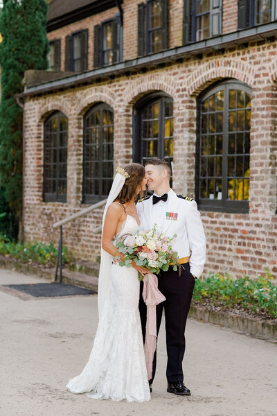 Military groom attire and a lace spaghetti strap wedding dress for couple portraits during Cocktail Hour