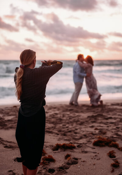 photographer taking picture of man and woman kissing on beach