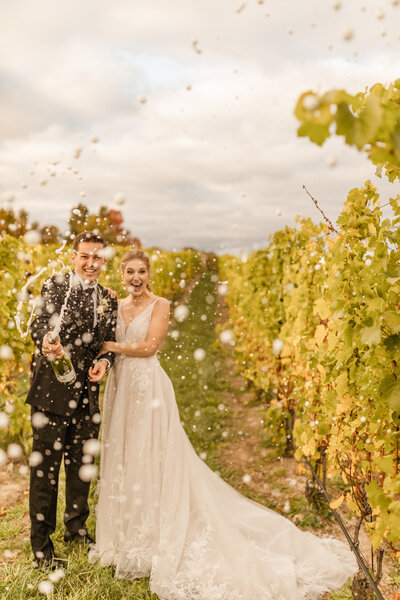 bride and groom popping champagne in vineyard